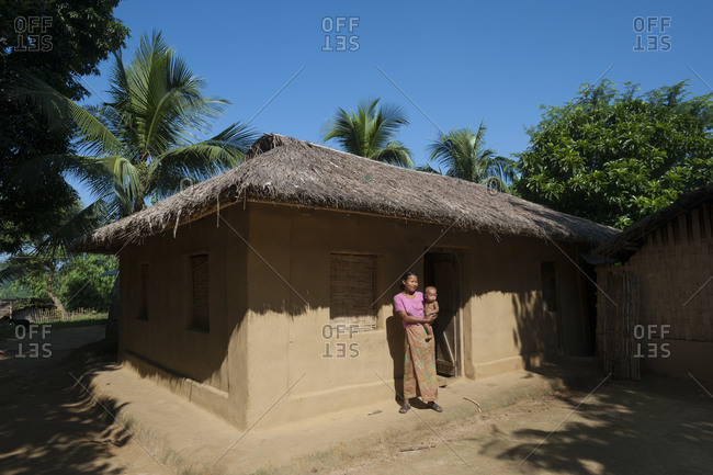 Mother and baby standing outside a traditional mud and thatch house