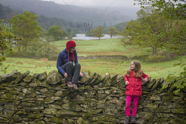 Mother and daughter rest on a dry stone wall while on holiday in The Lake District