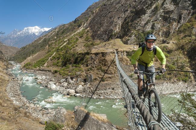 A mountain biker crosses a long steel suspension bridge in Nepal