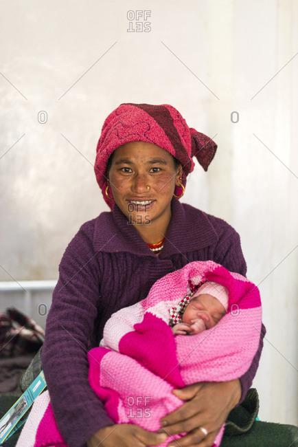 Okhaldhunga, Okhaldhunga district, Nepal - November 12, 2015: A happy mother smiles while holding her new born baby in blankets at Okhaldhunga Hospital