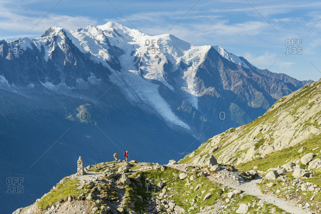 Hikers and the summit of Mont Blanc on the Tour du Mont Blanc trekking route in the French Alps