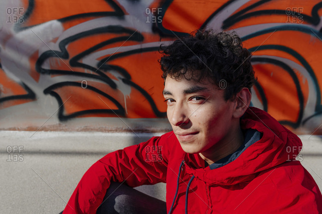 Young man wearing red hood sitting against wall