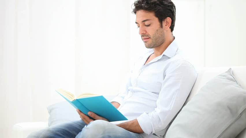 Smiling relaxed man reading a book sitting on sofa. Happy hispanic man relaxes at home with a  book. A guy takes the time to read a new book. University student studying sitting on the couch. | Shutterstock HD Video #10006733