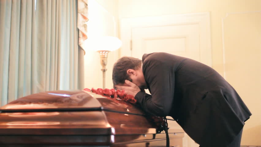 Man weeping over coffin at funeral wake service, grief of loss