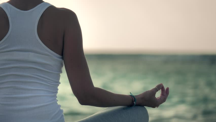 Woman sitting in yoga lotus pose on the caribbean beach, Mahahual, Mexico. 4k