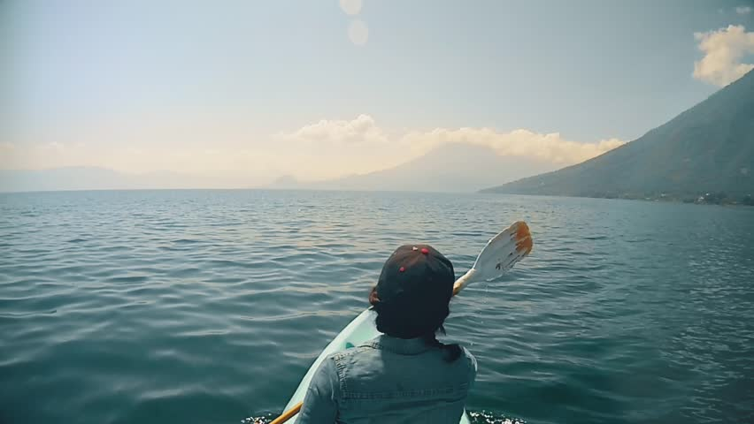 Woman kayaking on the Lake Atitlan towards the San Pedro volcano
