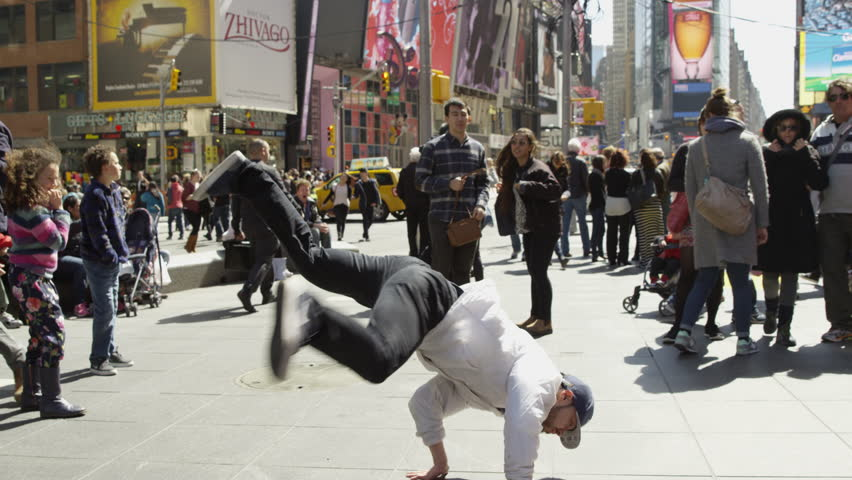 NEW YORK - APR 11, 2015: hip hop dancer, breakdancing, doing windmills in crowded Times Square, slow motion 4K in Manhattan, NY. Times Square is a major commercial intersection in NYC, USA.
