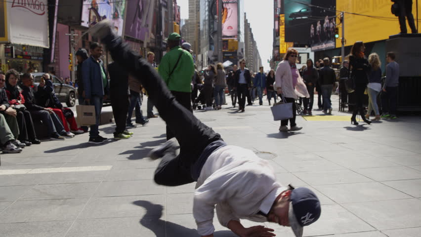NEW YORK - APR 11, 2015: b-boy doing windmills in Times Square; dancer breakdancing in public in slow motion 4k in Manhattan, NYC. Times Square is an iconic commercial intersection in NY, USA.