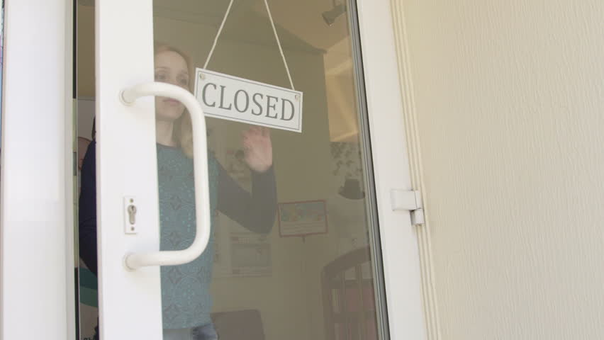 Woman business owner turning sign from closed to open on front door of the store | Shutterstock HD Video #10024742