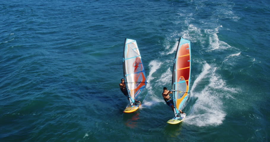 Cinematic aerial view of windsurfers sailing across the ocean