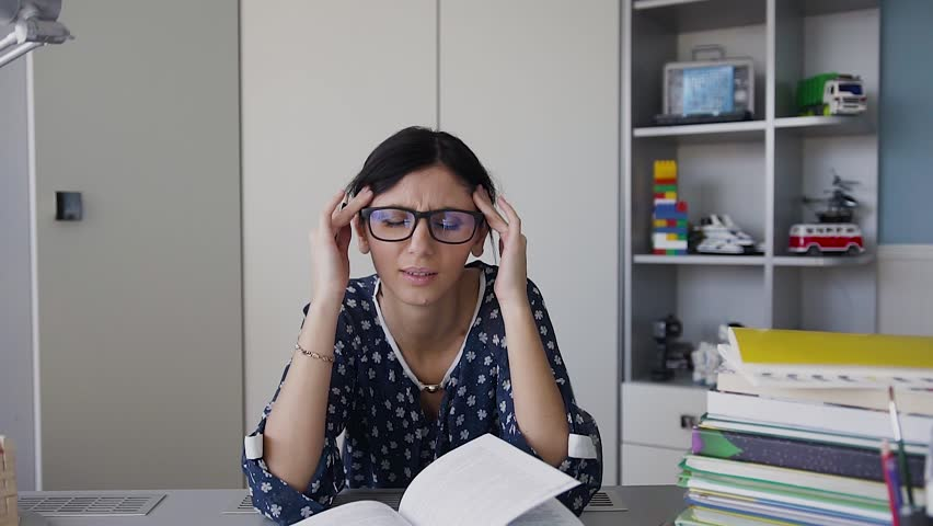 Young sad woman in glasses sitting at the working table with headache massaging her temples with circular motion, healthcare and stress concept slow motion | Shutterstock HD Video #1005607675