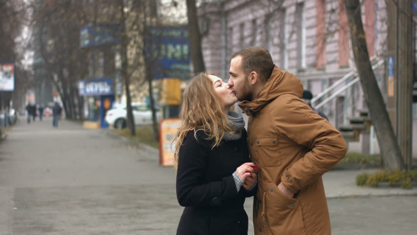 A young couple on a city street. The guy and the girl are standing together on the pedestrian street and talking. Then the guy gives his girl a small heart in which the ring. | Shutterstock HD Video #1005758902