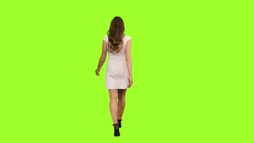 Back view young woman in white dress walking on green screen background, Chroma key, 4k footage