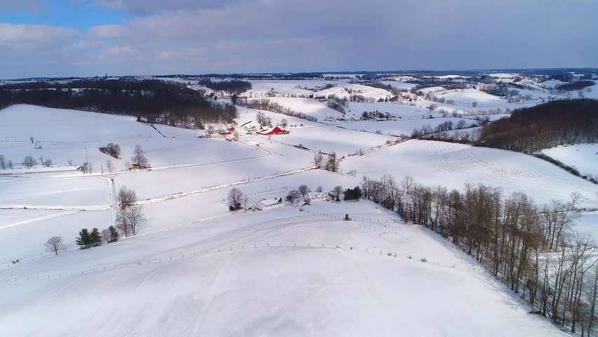 Aerial Amish farm winter with snow covered hills and blue sky