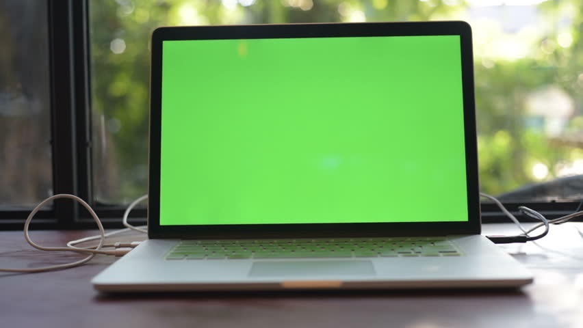Computer laptop with green screen on the table of cafe.   Shutterstock HD Video #1006625635