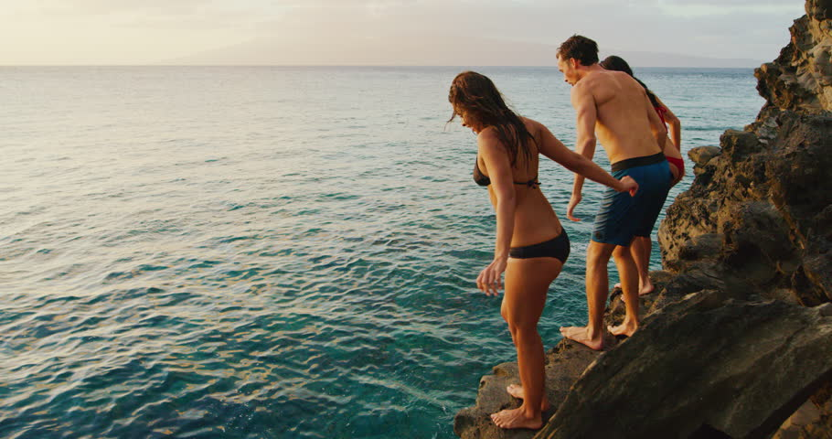 Friends cliff jumping into the ocean at sunset | Shutterstock HD Video #1006626088