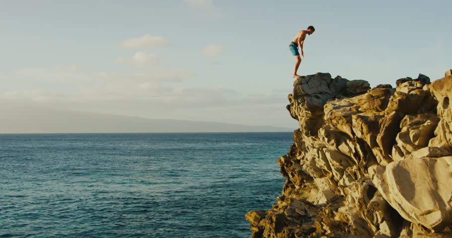 Young man doing backflip cliff jumping into ocean at sunset