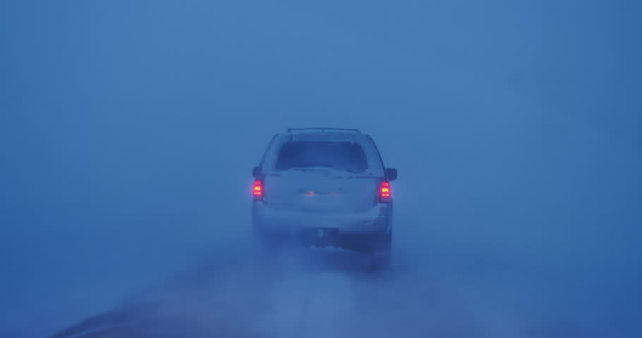 Following car tail lights in zero visibility high winds blizzard snow storm, Iceland.