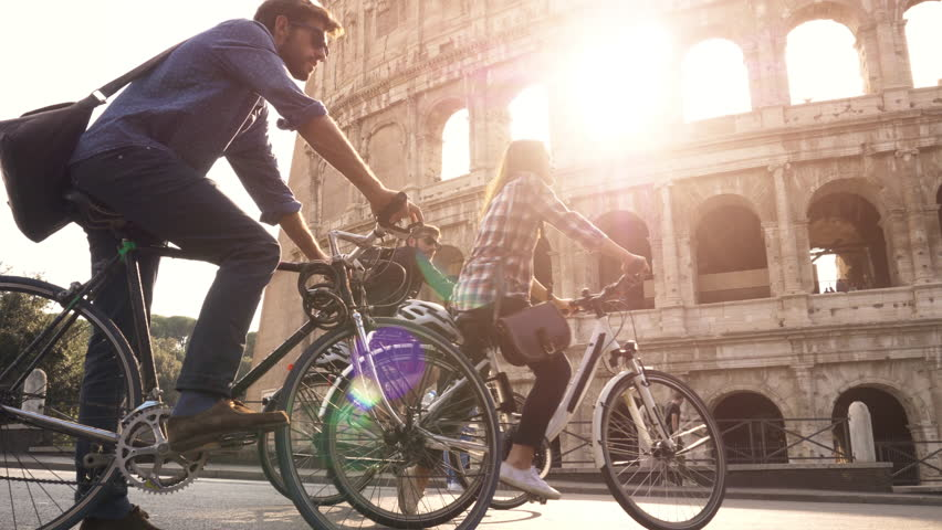 Three happy young friends tourists riding bikes with backpacks at Colosseum in Rome on sunny day slow motion camera steadycam
