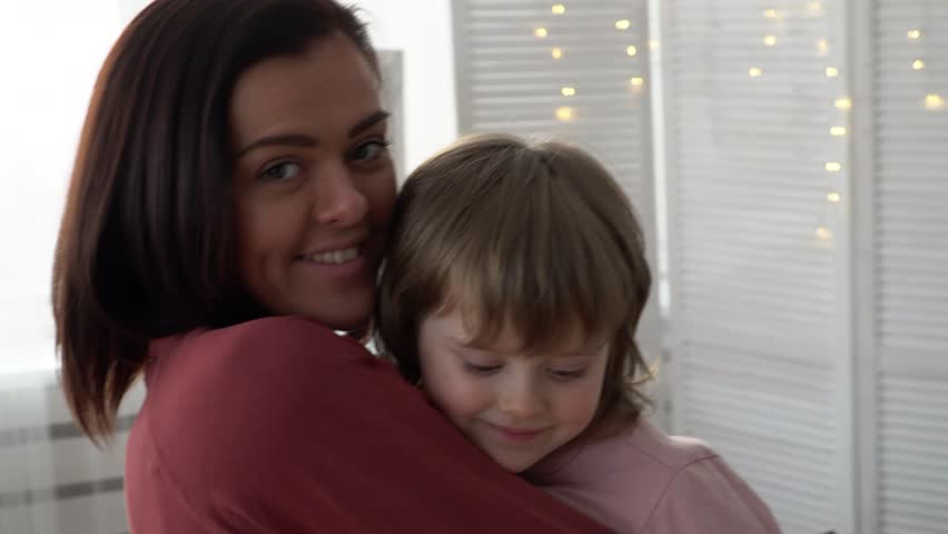 Happy young mother and her little daughter looks at a camera | Shutterstock HD Video #1006698973