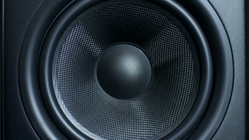 Close-up of black round audio speaker pulsating and vibrating from sound on low frequency. Contemporary stylish sub-woofer. #1006709959