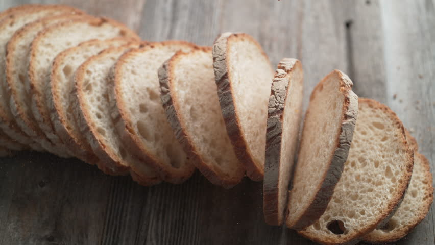 Sliced sourdough bread falling on a table. Shot with high speed camera, phantom flex 4K. Slow Motion. #1006716889