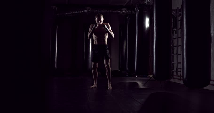 Kickboxer shadow boxing as exercise for the fight. Fighter training punching. Boxing in the darknes. Young boxer training in the gym | Shutterstock HD Video #1006718791