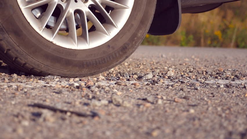 Wheel of car are slip on a asphalt road during start of movement. Small stones and dirt is fly out from under the tire of a auto. Slow motion close up