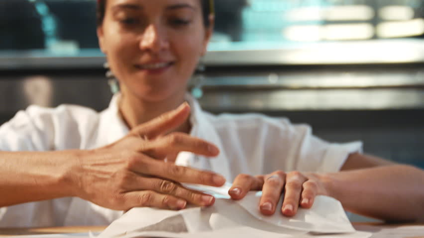 Young woman wrapping food for take away at a deli,cafe, close up