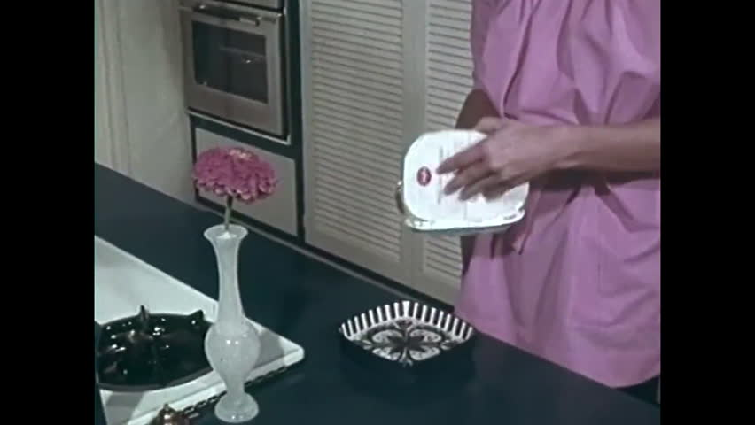 CIRCA 1970s - A woman is shown microwaving different kinds of frozen food in 1970.
