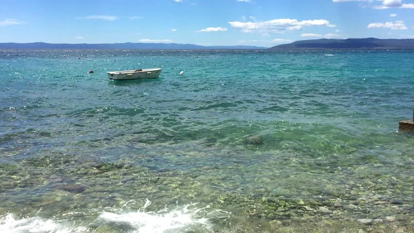 Small rental rowing boat floats on small waves of Adriatic Sea.Crystal clear water sparkling in the sun.Take a boat for rent on summer vacation.Place for swimming and diving during holiday trip Royalty-Free Stock Footage #1006739740