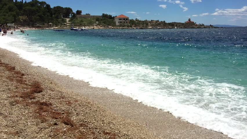 Popular tourist area on coast of beautiful Adriatic Sea in Croatia.Crystal clear water with deep blue and green color.Awesome travel destination for summer vacation travel.Sea waves rolling on beach Royalty-Free Stock Footage #1006739935