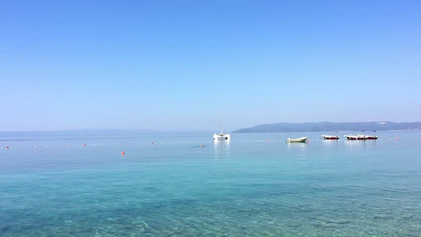 Small rental yacht &rowing boats drift on small waves of beautiful Adriatic Sea in Croatia.Crystal clear sea water at resort.Great place for scuba diving,snorkeling,swimming on summer vacation trip Royalty-Free Stock Footage #1006740076