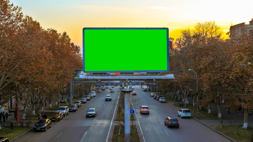 A billboard with green chroma key on the background of fast moving cars at sunset. 4K Time Lapse video