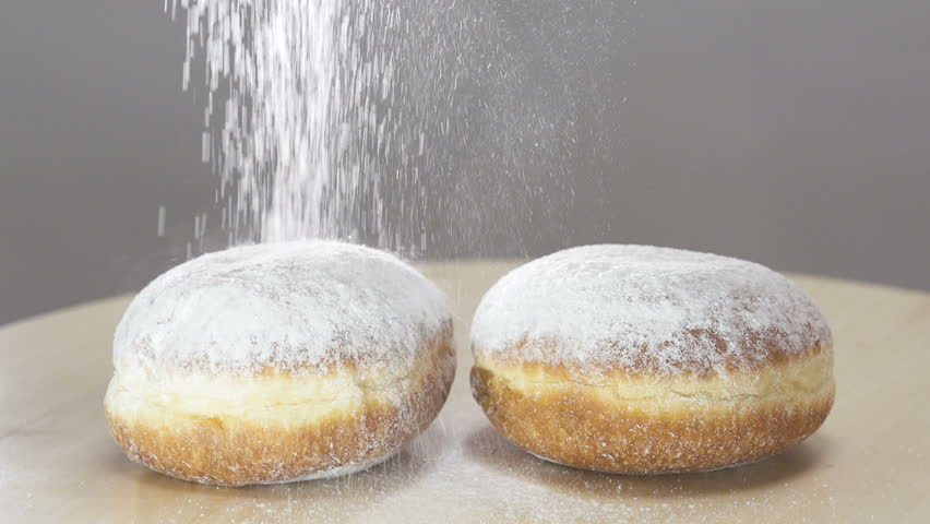Spreading Sugar Powder On Hanukkah Doughnuts . Slow motion