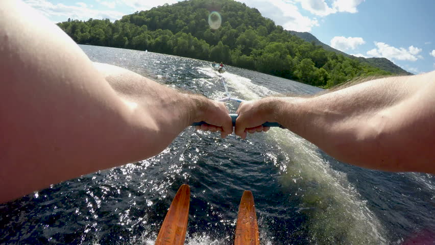 POV of young man water skiing on vintage wooden water skis a clear blue mountain lake with lens flare