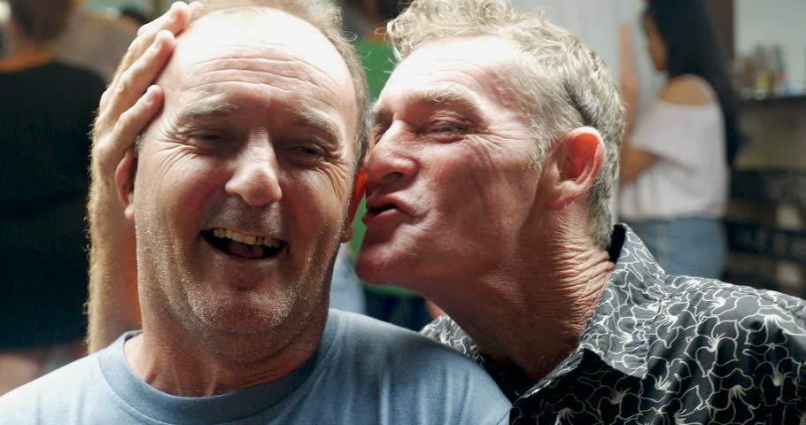 Profile of two affectionate men and joking with each other at a party or bar pub