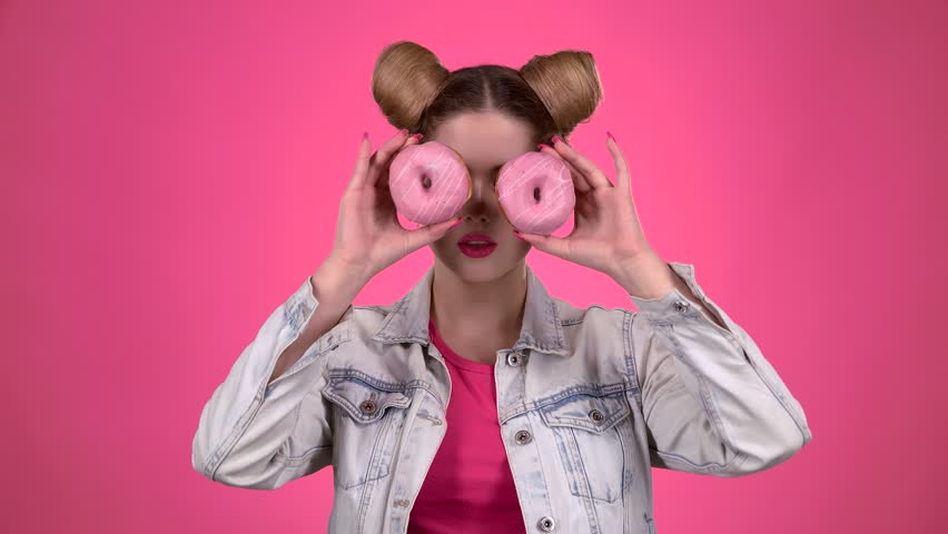 Girl sniffs the cake and licks her lips. Pink background. Slow motion   Shutterstock HD Video #1006807264