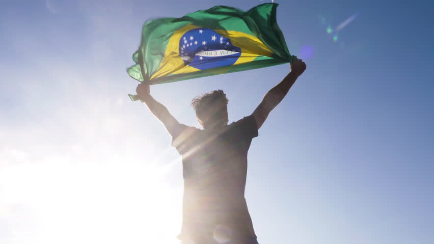 Young man holding brazilian national flag to the sky with two hands at the beach at sunset
