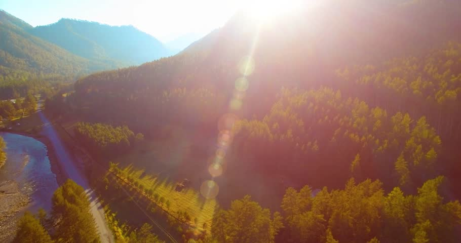 Aerial UHD 4K view. Mid-air flight over fresh mountain river and meadow at sunny summer morning. Green trees and sun rays on horizon. Rural dirt road below. #1006834747