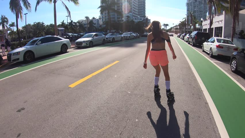 Trendy girl roller-skating on Miami South Beach road
