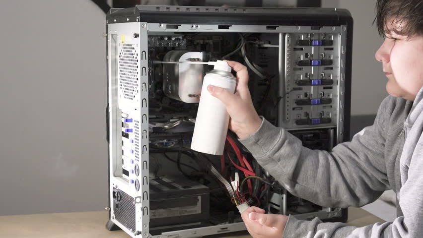 A Computer Geek Boy Cleaning Computer With Compressed Air   Royalty-Free Stock Footage #1006845559