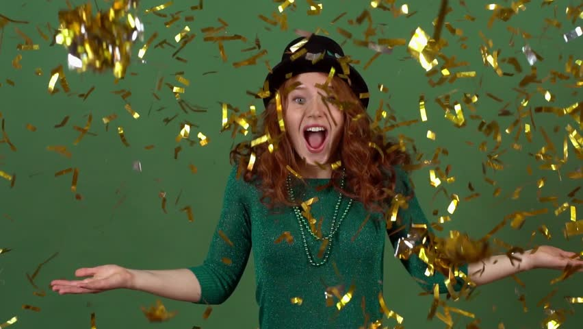 Young woman celebrating saint patrick's day on green wall moving in confetti