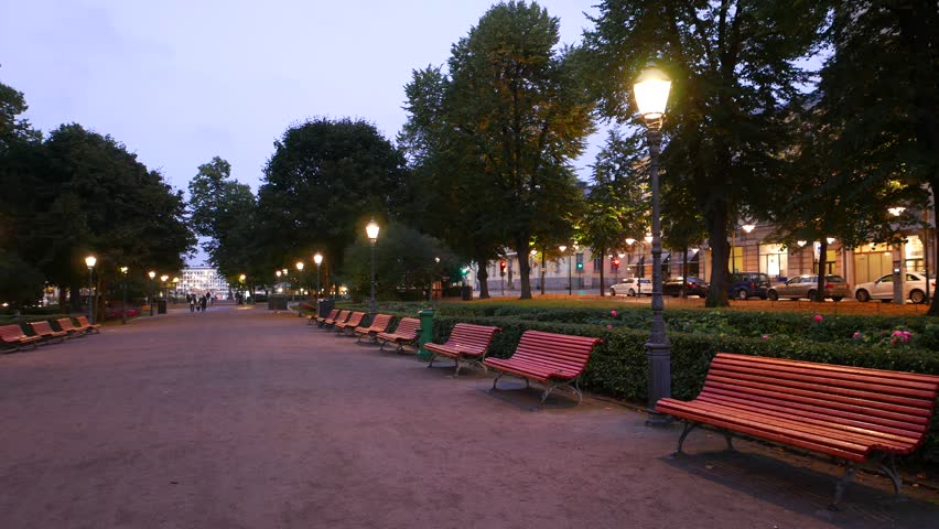 Empty wide walkway of Esplanadi park at evening twilight, wooden benches along pedestrian promenade. No people at this time, lanterns light and yellow warm illumination on street | Shutterstock HD Video #1006853638