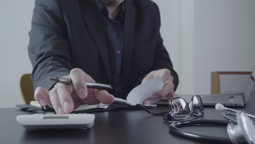 Medical finance and network concept.Doctor hand working with calculater and laptop computer on wood desk in slow motion | Shutterstock HD Video #1006854121