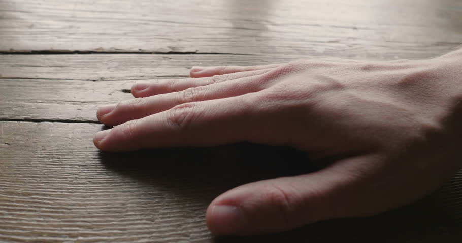 Close-up of a hand touching a wooden piece of furniture to feel its consistency and the precious material with which it was built. Concept of: love for nature, wood.
