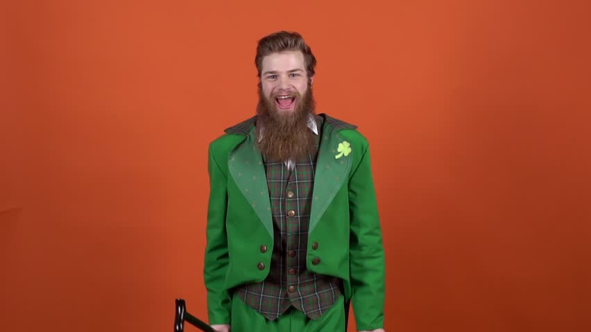 Young man leprechaun celebrating saint patrick's day isolated on orange wall holding stick and hat