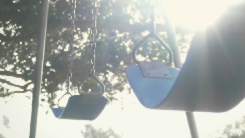 Empty swings at child playground closeup loop