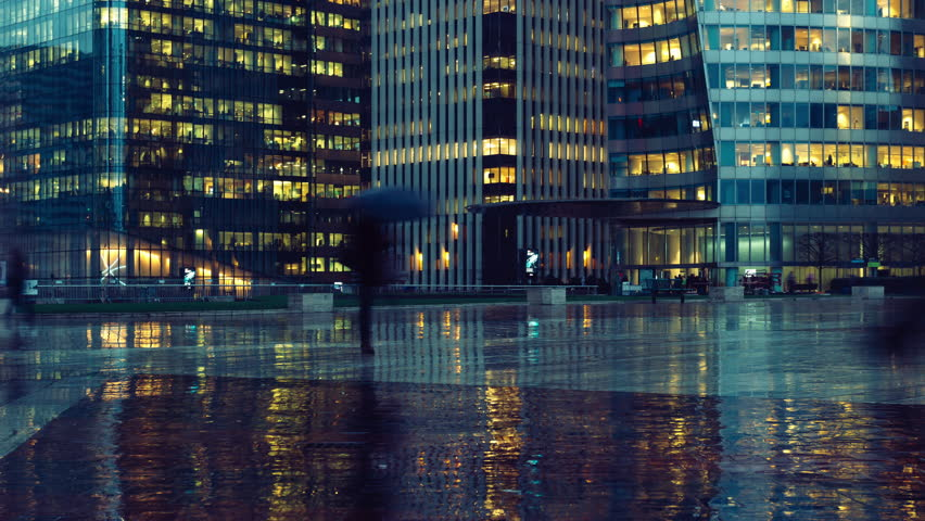 Time lapse of crowd of people walking near modern buildings in Paris business district La Defense. Night city lights, illuminated windows of office center. Concept of big city, business, job, economy