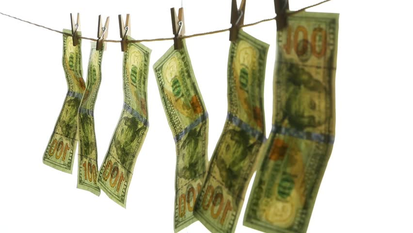 Dollar banknotes hang on a rope with clothespins. The concept of dirty money.  | Shutterstock HD Video #1006937554